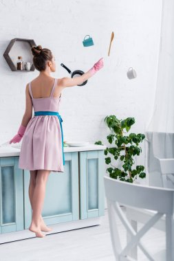 young elegant woman in rubber gloves levitating in air with cooking utensils in kitchen