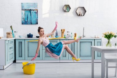 shocked girl in apron levitating with mop and yellow heeled shoe during house cleaning in kitchen