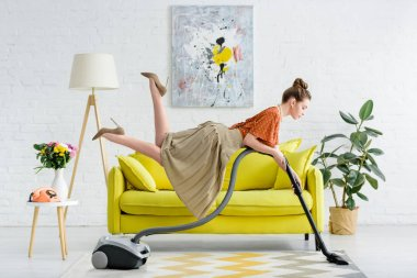 side view of elegant concentrated young woman levitating in air and vacuuming rug in living room