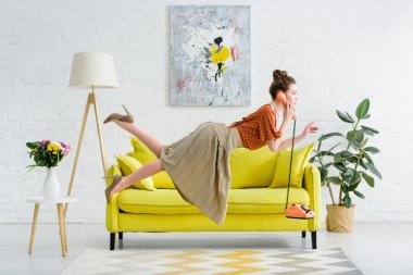 side view of elegant young woman levitating in air and talking on vintage telephone in living room