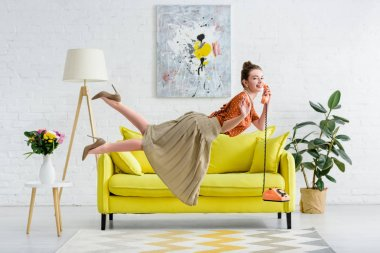 side view of happy elegant young woman levitating in air and talking on vintage telephone in living room