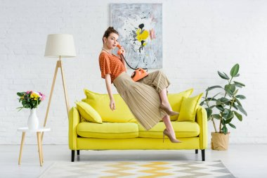 elegant young woman levitating in air and talking on vintage phone in living room