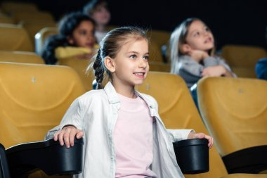 Attentive smiling child watching movie in cinema with multicultural friends stock vector
