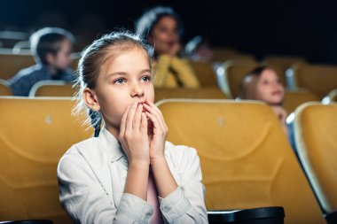 cute worried child watching movie in cinema together with multicultural friends