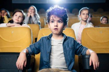 concentrated mixed race boy watching movie in cinema together with multicultural friends