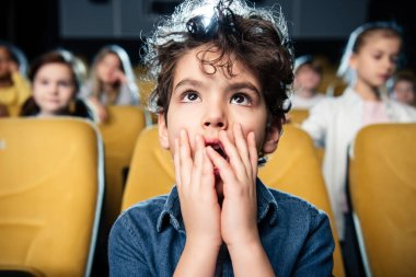 Selective focus of surprised mixed race boy watching movies together with friends stock vector