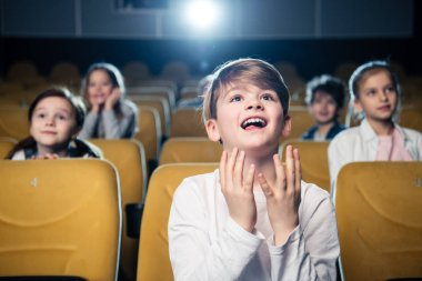 amused emotional boy watching movie together with multicultural friends