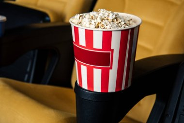 Selective focus of cinema seat with stripped paper cup of popcorn in cup holder stock vector