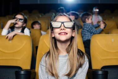 selective focus of cute smiling child in 3d glasses sitting with friends in cinema