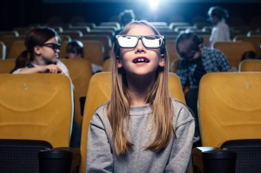 Adorable child in 3d glasses watching movie in cinema together with friends stock vector