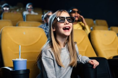 Happy excited child in 3d glasses watching movie in cinema stock vector