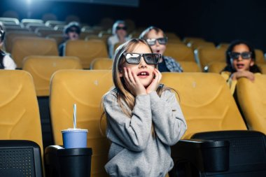 multicultural friends in 3d glasses watching movie in cinema