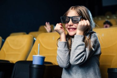 Emotional child in 3d glasses watching movie while sitting near paper cup stock vector