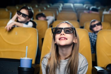 Smiling blond child in 3d glasses sitting near paper cup and watching movies in cinema stock vector