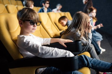 multicultural friends in 3d glasses sitting in comfortable seats in cinema