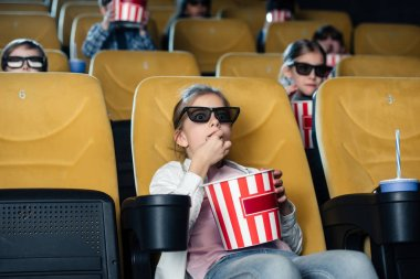friends watching movie and eating pop corn in cinema together
