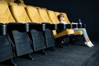 Selective focus of child sitting in cinema seat in empty row stock vector