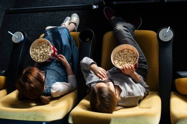 overhead view of friends eating popcorn and watching movie in cinema