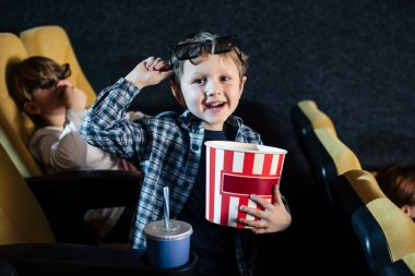 Selective focus of smiling boy holding paper cup of popcorn and looking at camera stock vector