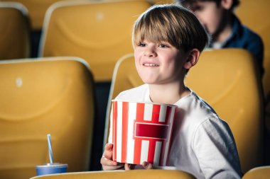 Adorable smiling boy holding stripped paper cup while watching movie in cinema stock vector