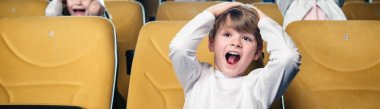 panoramic shot of excited boy screaming while watching movie in cinema