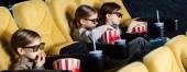 Panoramaaufnahme von Kindern, die einen Film in 3D-Gläsern ansehen und Popcorn im Kino essen