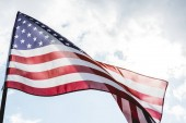 low angle view of national american flag with stars and stripes against sky with clouds