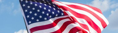 panoramic shot of american flag with stars and stripes against blue sky