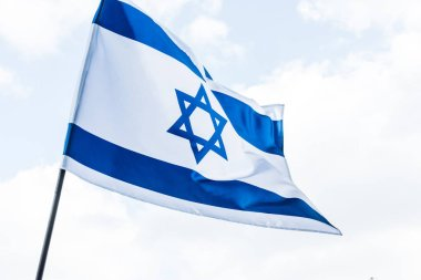 low angle view of national flag of israel with star of david against sky with clouds