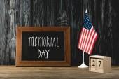 tabule s pamětním dnem v blízkosti americké vlajky a dřevěných kostek s datem