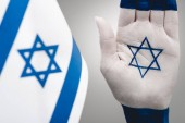 selective focus of female hand with star of david near flag on grey