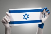 cropped view of female hands holding national flag of israel on grey