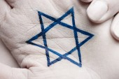 close up of female hands with jewish star of david on grey