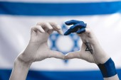 Photo cropped view of female hands with star of david showing heart near flag