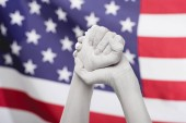 cropped view of female clenched hands painted in white near american flag
