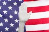 oříznutý pohled ženské ruky malované v bílém blízko americké vlajky