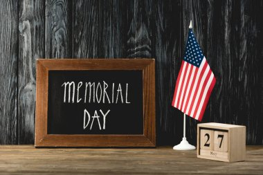 Chalkboard with memorial day lettering near american flag and wooden cubes with date stock vector