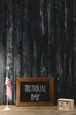 Chalkboard with memorial day lettering near american flag and cubes with date stock vector