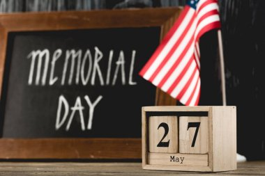 wooden cubes with date near chalkboard with memorial day lettering and american flag
