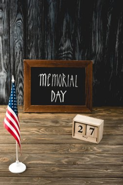 chalkboard with memorial day lettering near wooden cubes with date and flag of america