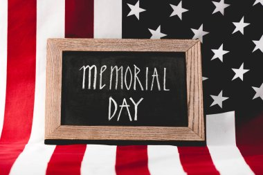 Chalkboard with memorial day lettering near flag of america with stars and stripes stock vector