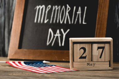 Wooden cubes with date near flag of america with stars and stripes and memorial day lettering on chalkboard stock vector