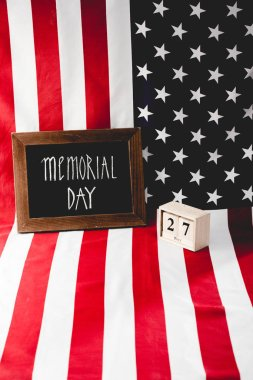 memorial day letters on chalkboard near wooden cubes with date and flag of america