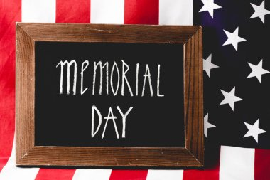 chalkboard with memorial day letters near flag of america