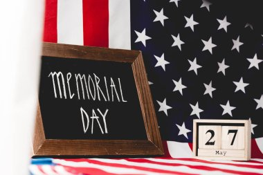 Black board with memorial day letters near flag of america and cubes with date stock vector