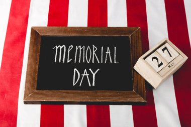 memorial day letters on black board near wooden cubes with date