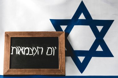 chalkboard with hebrew lettering near blue star of david on national flag of israel