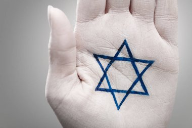 Close up of female hand with star of david on grey stock vector