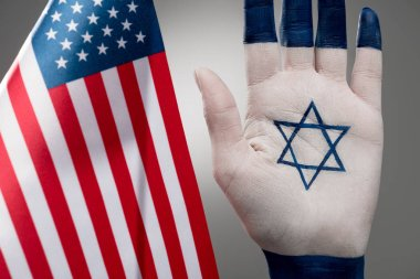 selective focus of female hand with jewish star of david near american flag on grey