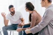 ženy a muži sedí a mají diskuse během zasedání skupinové terapie